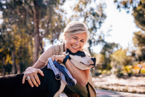 Mature woman hugging her dog outdoors