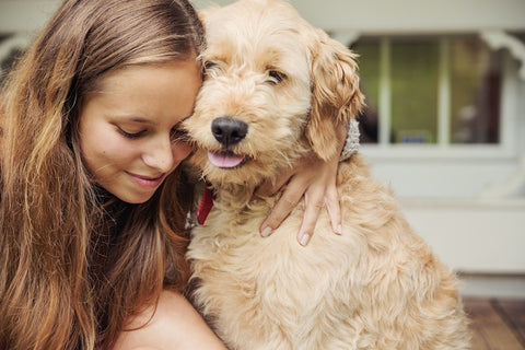 teenage girl lovingly hugging dog