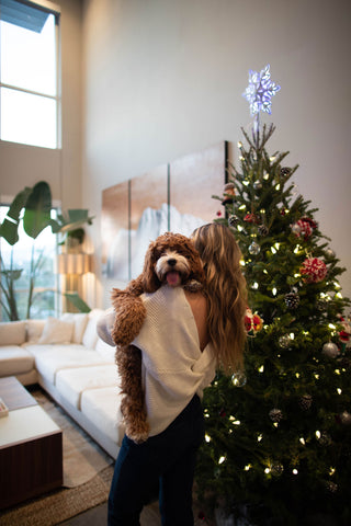Woman carrying puppy in front of Christmas tree