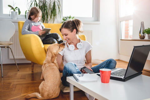 Woman sitting on the floor petting dog at home while daughter sits on the armchair using tablet