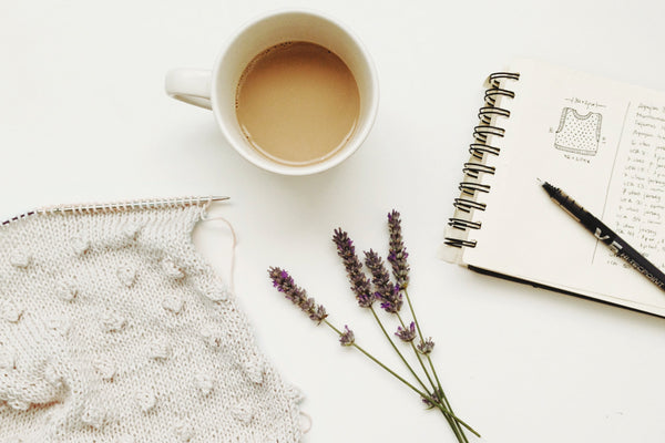 Lavender on desk with coffee and sketchbook