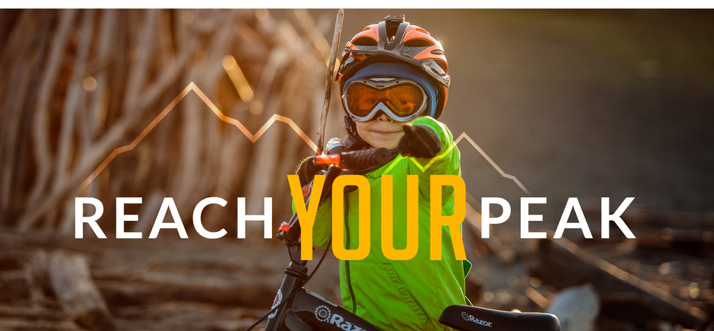REACH YOUR PEAK - Mountain Graphic Behind Headline - Little Boy in Capstone gear pointing out towards you