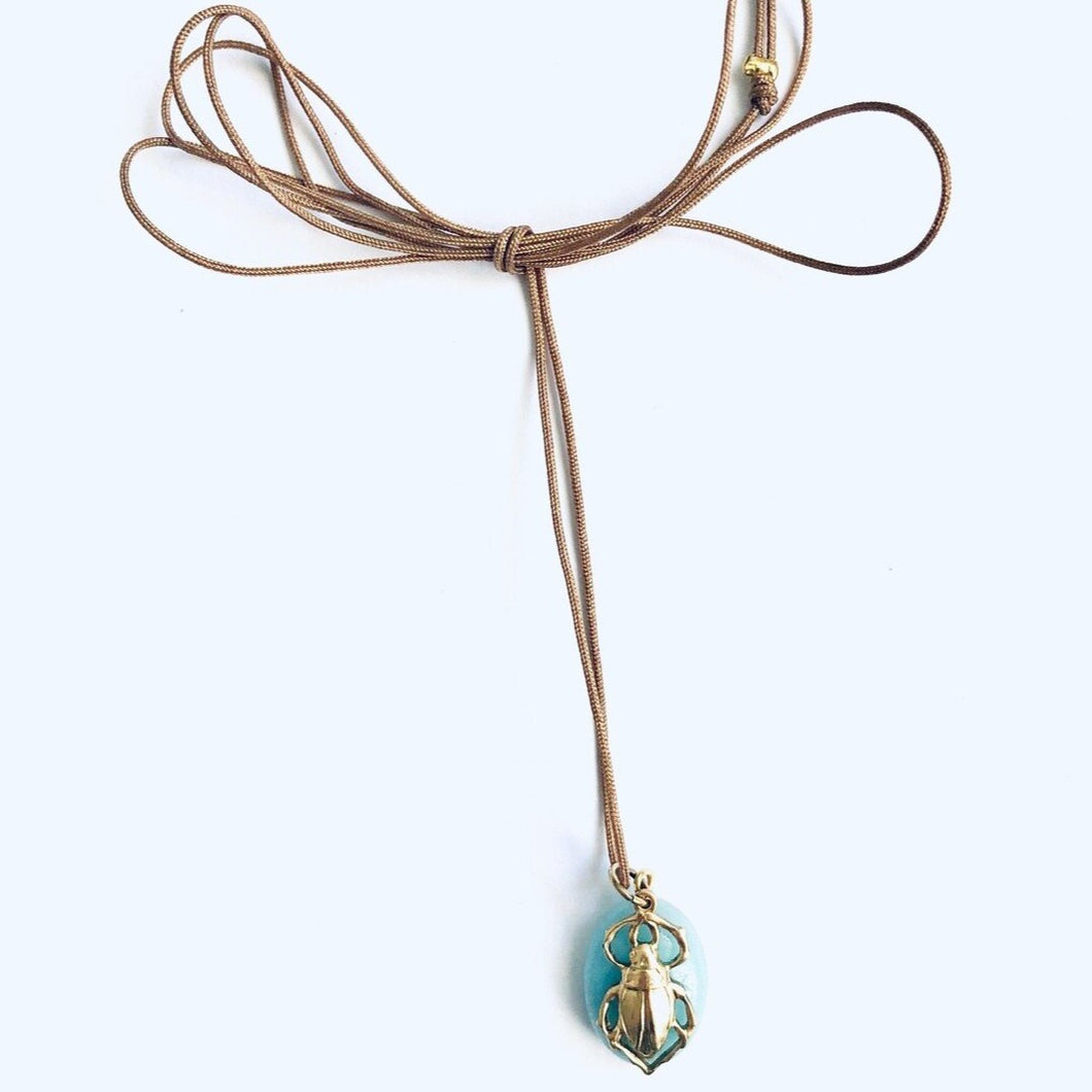 hanger of brass beetle on a blue stone