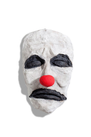 bronze sculpture of face of a clown in white red and black