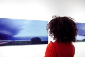picture of woman looking at a supercell photo at gallery exhibition