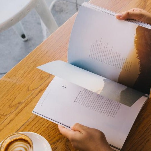 cup of appucinno and Bible book with beautiful illustrations and photography