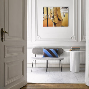 hallway with marble floor, gey upholstered bench and yellow art photo