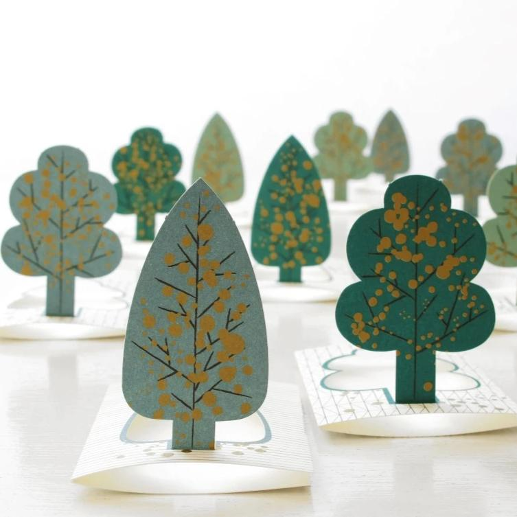 paper pop up seating cards of trees with gold spatters