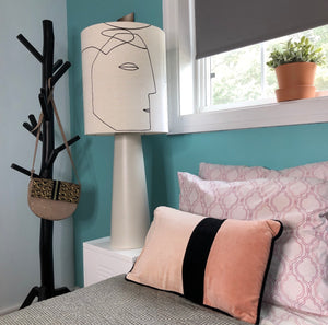 table lamp with face next to a bed in contemporary setting