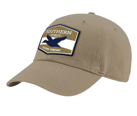 "A driftwood Southern Strut original hat with a hexagon patch with a top and bottom brown strip and a white one separating it. At the top ""Southern Sturt,"" underneath that a silhouette of a duck."