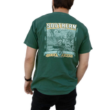 "Printed on a Comfort Color emerald colored t-shirt the Southern hunting design is an elegant english setter laying in a marsh patch, with an over and under shotgun laying in front. In the back, there are two ducks ascending. At the bottom, in a banner style, ""Don't Forget Your Calling"""