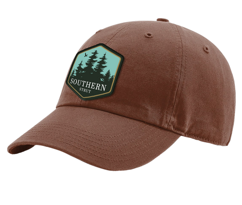 "A brown Southern Strut original hat with a hexagon patch with a pine forrest design and at the bottom ""Southern Sturt"""