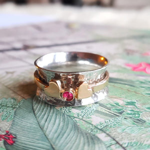 Spinning ring with two gold hearts surrounding gemstone
