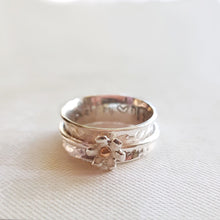 Load image into Gallery viewer, Silver daisy spinning ring with solid gold detail at its centre.