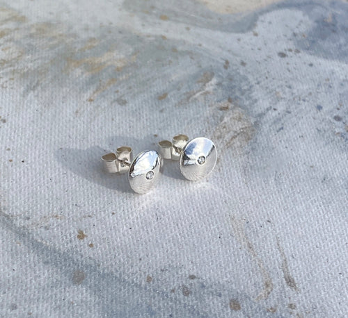 Domed silver earrings with diamonds.