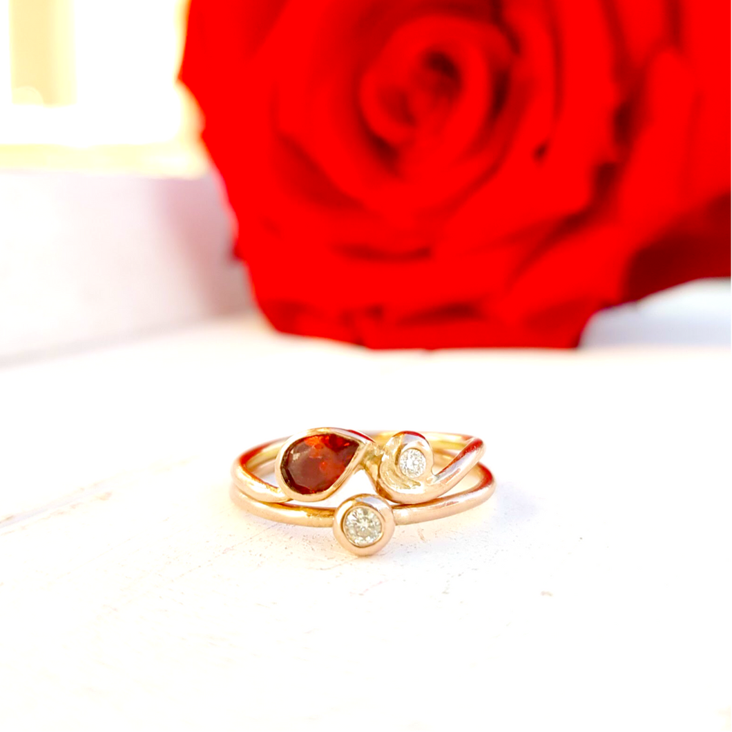 Gold stacking ring set with garnet and diamonds.