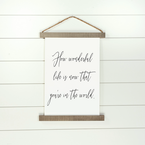 Hanging canvas sign with quote How Wonderful Life Is