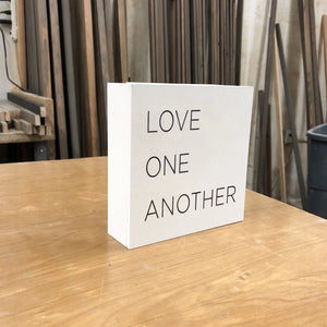 Side view of small box sign Love One Another