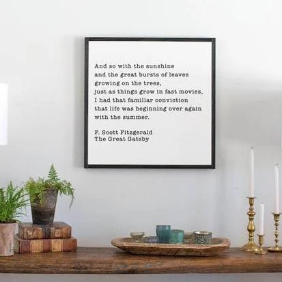 Black and white wood sign with Great Gatsby quote