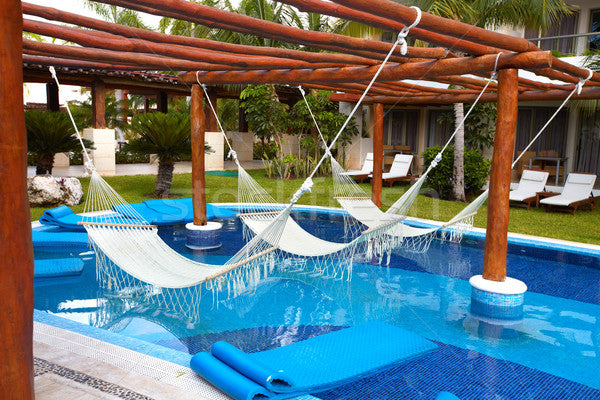 Hammocks hung over swimming pool