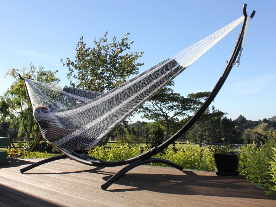 Black and white hammock in metal arc hammock stand