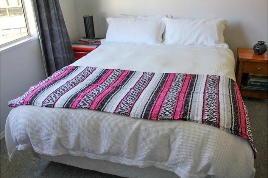 Striped Pink Woven Mexican Blanket half folded on bed
