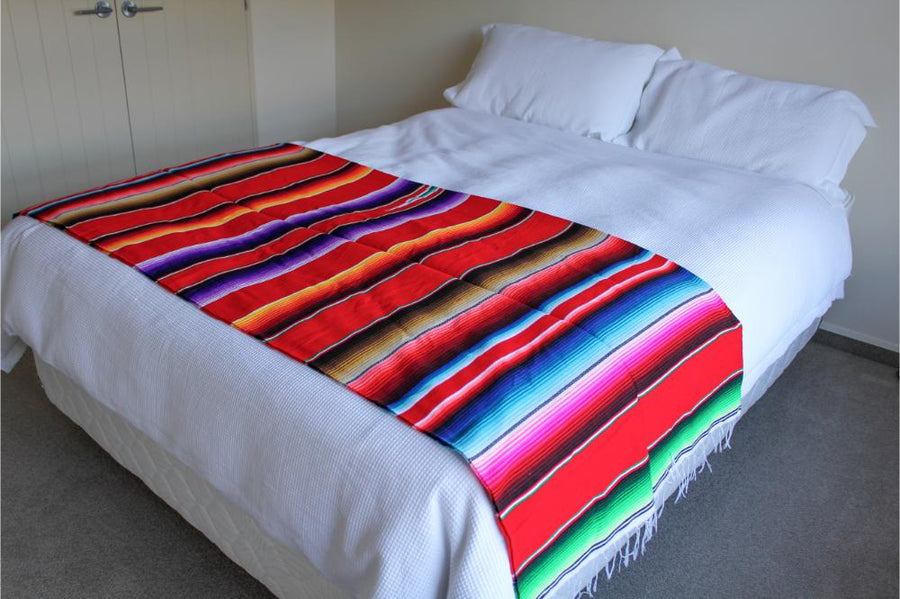 Red Mexican throw on bed