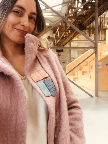blond woman with coat pink and patches