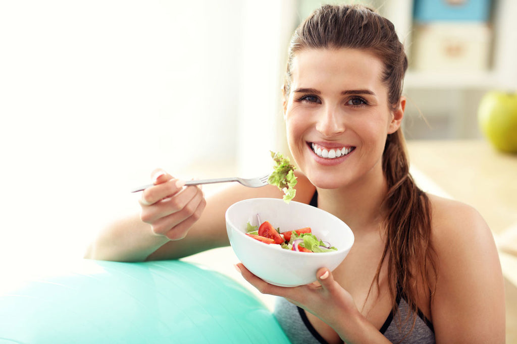 Image of a woman smiling and eating a salad
