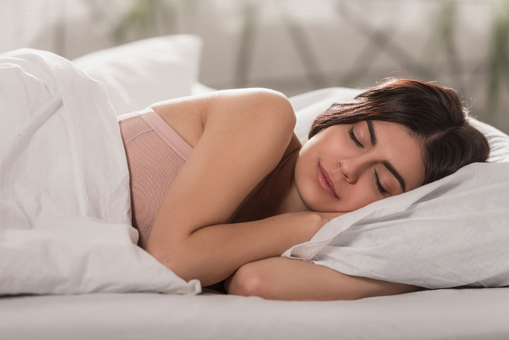 Photo of a brunette woman wearing a pink top sleeping with a white blanket and pillow