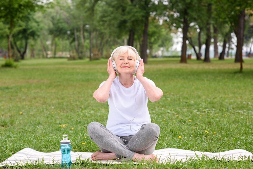 Image of a senior woman listening to relaxing music and doing yoga in a park