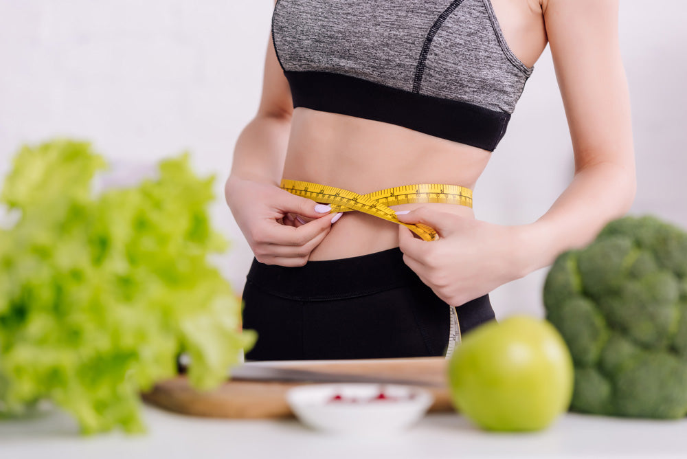 Image of a woman measuring her waist in front of a counter with healthy food
