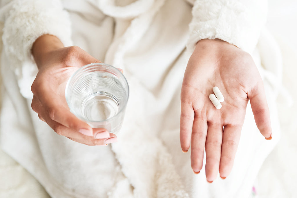 Image of a woman's hands holding probiotic capsules and a glass of water