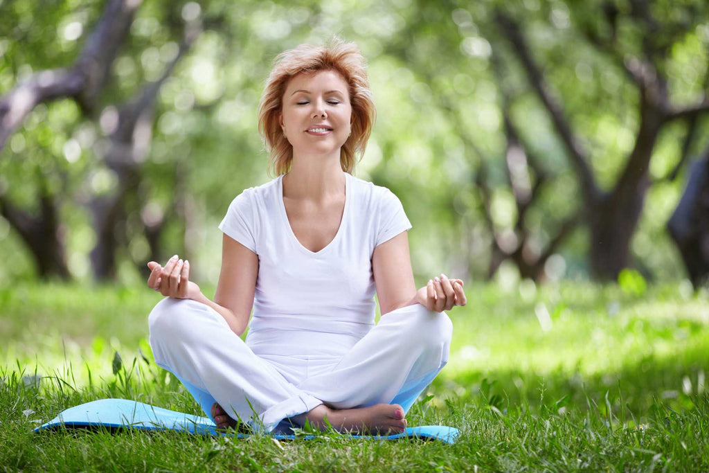 Image of a woman meditating in white on a sunny day on grass with trees behind her