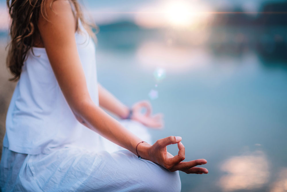 Image of a woman meditating by a lake at sunset to improve nutrient absorption