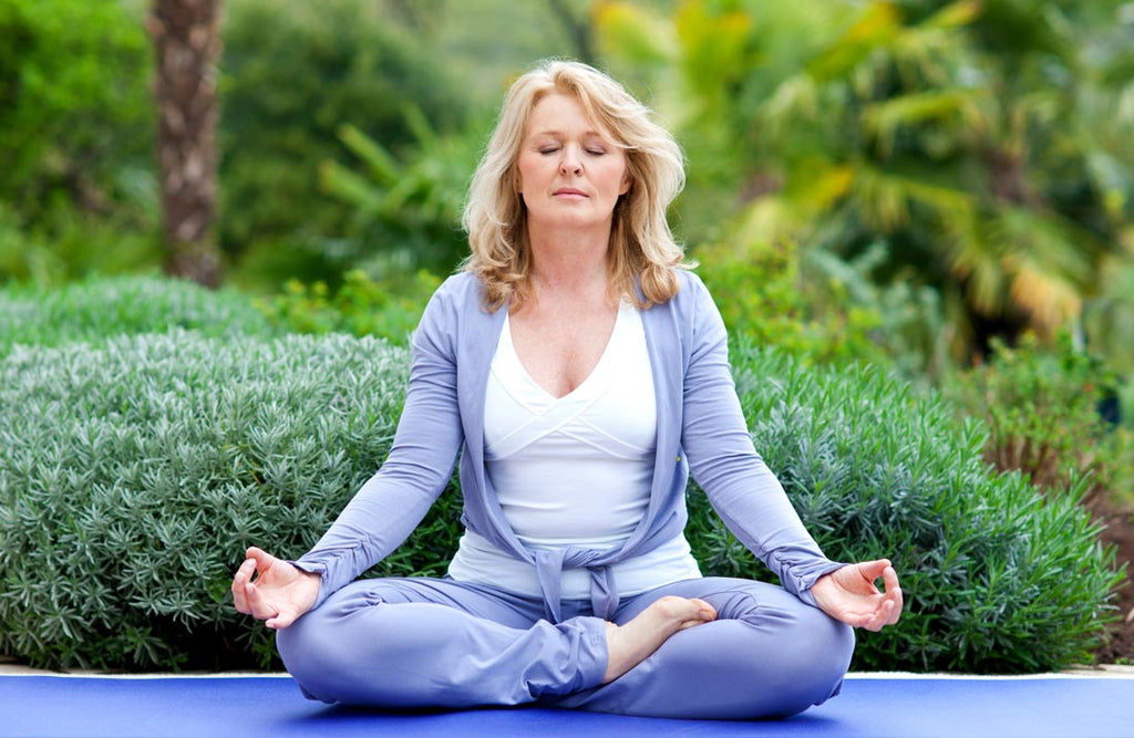 Image of an older woman doing meditation as a natural stress relief remedy