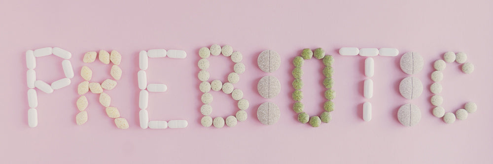 Image of 'prebiotic' spelled out in brown pills on a pink surface