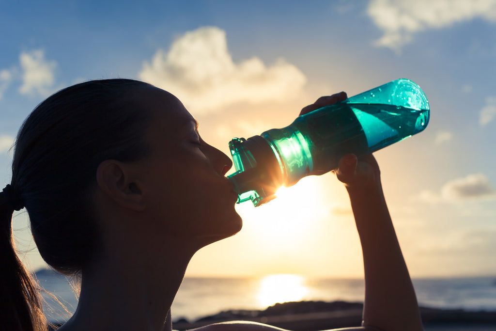 Photo of a woman drinking from a water bottle out on a sunny day