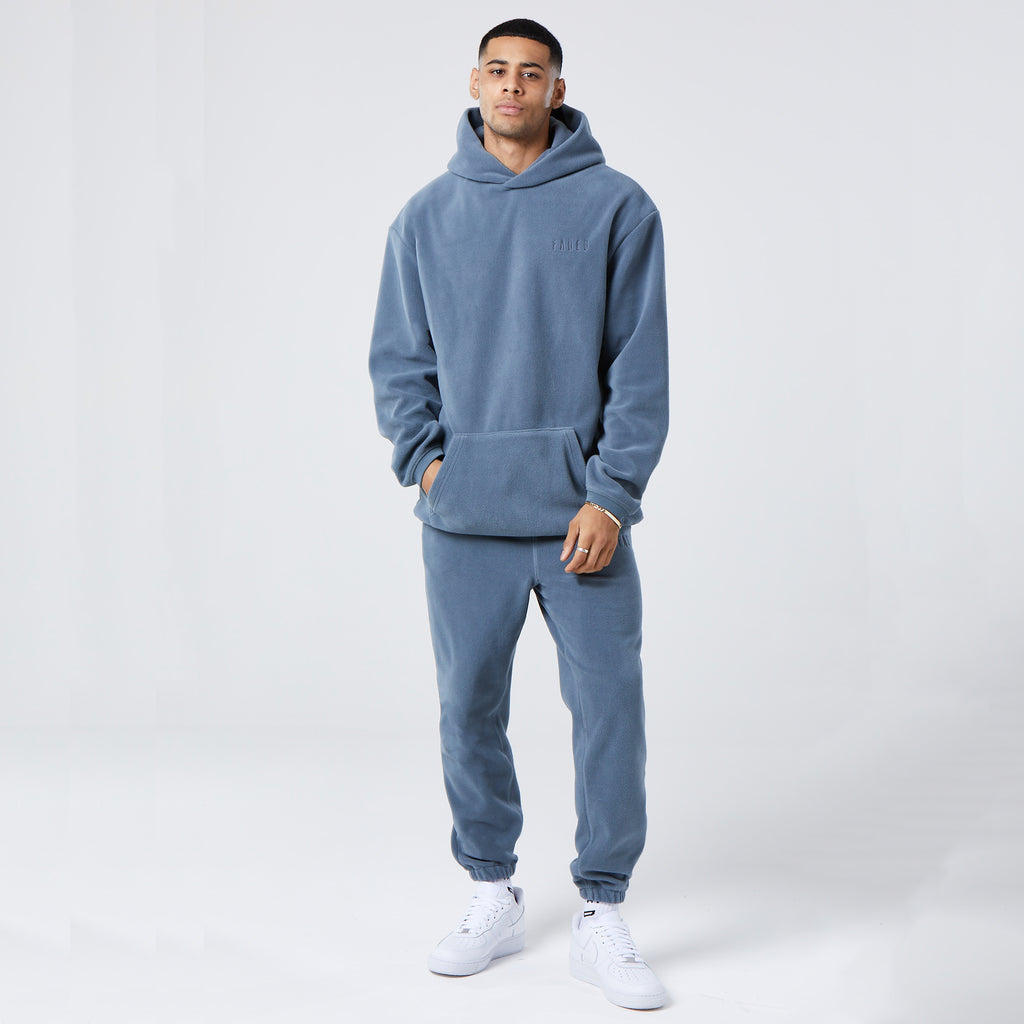 model wearing mens full tracksuit in washed teal fleece material