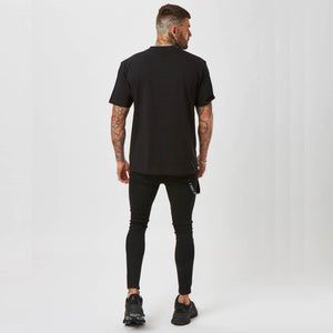 Reverse image of model wearing black graphic tee