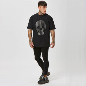 Model wearing studded skull graphic top