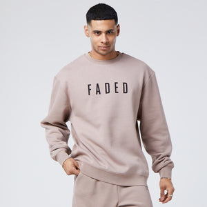 male model wearing a faded branded jumper in brown