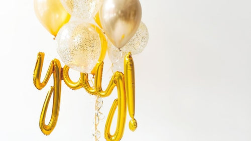 gold balloons spelling out yay