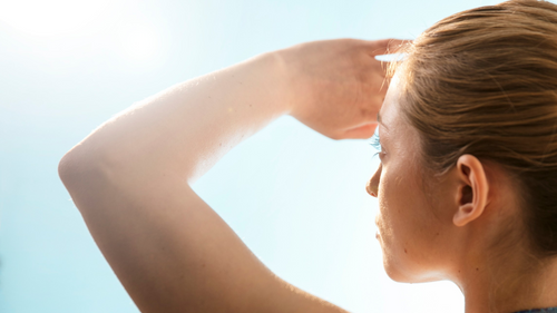 woman staring into sun covering eyes