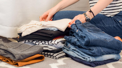 person-folding-clothes-in-piles