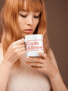 red hair lady holding a coffee mug with two hands and wearing a light pink sweater