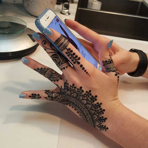 fresh jagua traditional hand mehndi design on girl holding iphone.