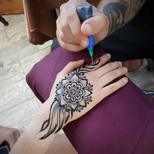 Design of henna - Henna artists doing traditional hand henna tattoo.