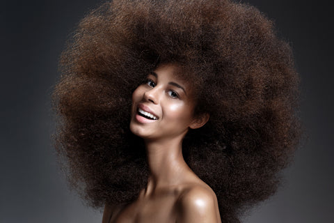 woman with giant afro smiling happy