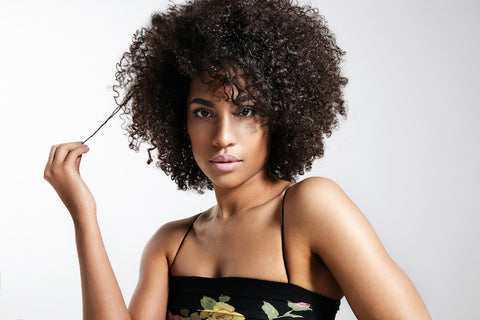 woman with curly afro pulling a strand of hair